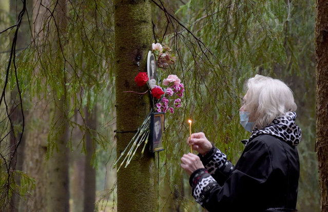 A woman visits the memorial, where the victims of Soviet dictator Joseph Stalin's regime were buried in the woods on the outskirts of Saint Petersburg, on October 30, 2020. Russia observed today Day of Victims of Political Repressions as people honoured the memory of the thousands of victims perished in the repressions of the Soviet Communist regime. (Photo by Olga Maltseva/AFP Photo)