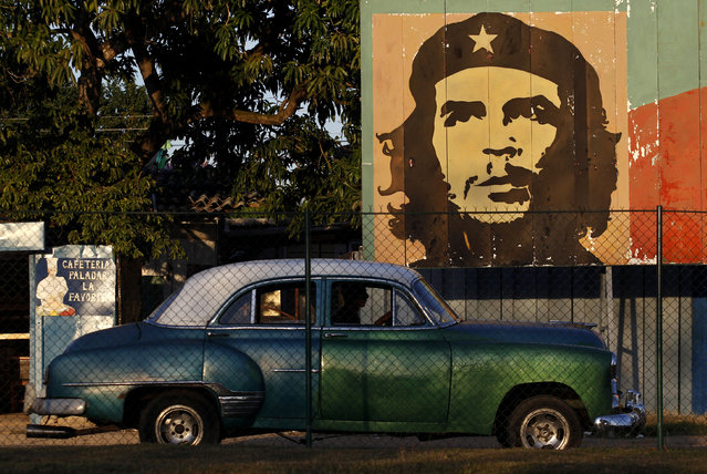 A car drives past a mural of revolution leader Che Guevara in Havana, January 8, 2012. (Photo by Enrique De La Osa/Reuters)