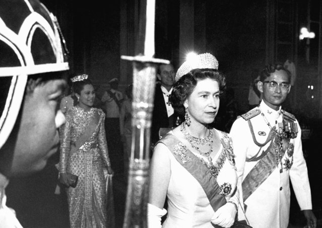 In this February 11, 1972, file photo, Britain's Queen Elizabeth II walks with Thailand's King Bhumibol Adulyadej, right, with Queen Sirikit at rear left and Prince Philip at rear right, in Bangkok. (Photo by AP Photo)