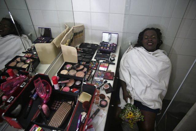 A bride from the Santa Marta slum takes a break after getting her makeup done before a group wedding in Rio de Janeiro December 17, 2014. A total of 16 couples took part in a mass wedding ceremony organized by the Police Peacekeeping Unit (UPP) as part of activities geared towards social enhancement of the slums. (Photo by Pilar Olivares/Reuters)