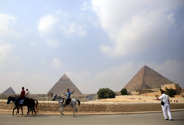 A policeman (R) argues with a man on a horse in front of the Sphinx at the Giza Pyramids on the outskirts of Cairo, Egypt, November 8, 2015. (Photo by Amr Abdallah Dalsh/Reuters)