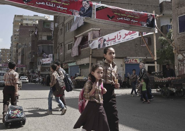 """Egyptian school children make their way home after school in front of a banner with the photo of a parliamentary candidate,top center, and Arabic that reads, """"running for the youth, together on the right path, Sayed Al-Minaay,"""" on a street in Boulaq El Dakrour district of Giza, near Cairo, Egypt, Thursday, October 8, 2015. (Photo by Nariman El-Mofty/AP Photo)"""