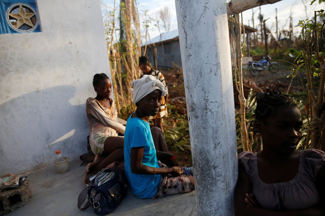People sit in front of their destroyed house after Hurricane Matthew hit Jeremie, Haiti, October 15, 2016. (Photo by Carlos Garcia Rawlins/Reuters)