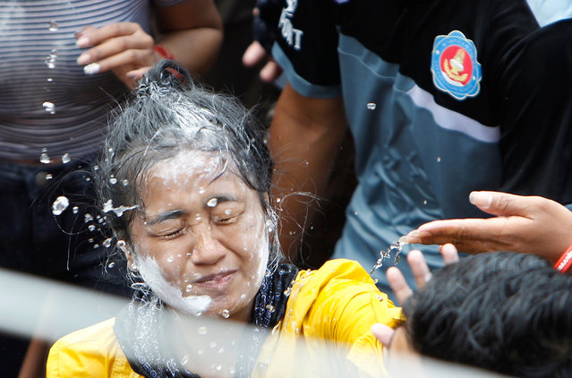 A girl is painted her face as she gets the holy water poured on her by her friends to mark the end of the Khmer New Year on the outskirts of Phnom Penh, Cambodia, Sunday, April 22, 2018. Buddhist followers received the holly water which is believed to bring good luck. (Photo by Heng Sinith/AP Photo)