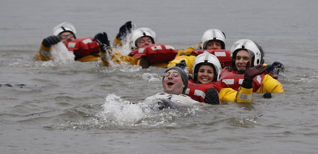 Swimmers in fancy dress swim with members of the Royal National Lifeboat Institution (RNLI) as they participate in the New Year's Day Loony Dook swim at South Queensferry, Scotland, January 1, 2015. (Photo by Russell Cheyne/Reuters)