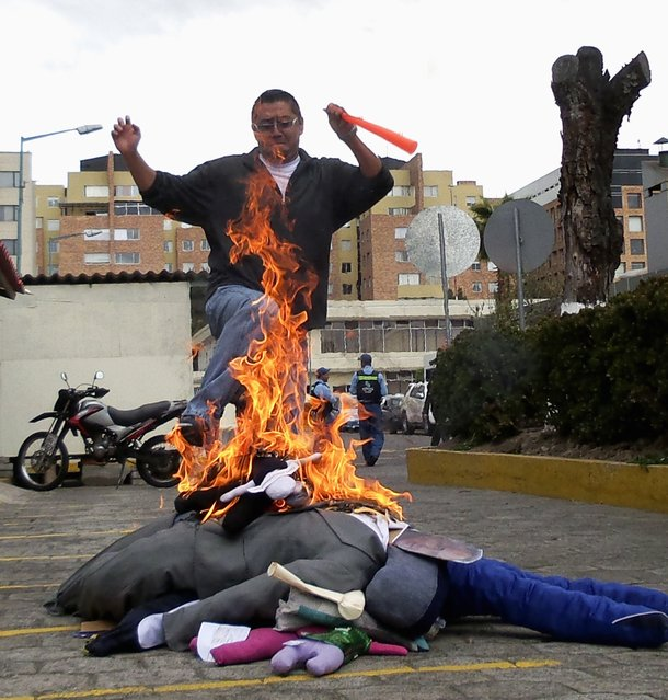 Revelers burn a pile of handmade puppets to kick and jump over, on the streets of Quito December 31, 2014. (Photo by Guillermo Granja/Reuters)