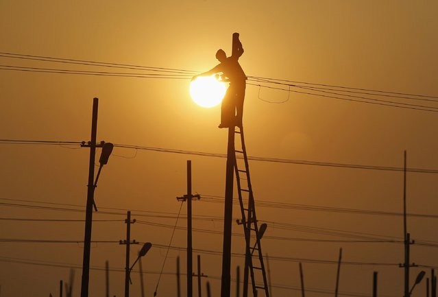 A worker is silhouetted against the setting sun while installing an overhead electric cable pole on the banks of river Ganges in the northern Indian city of Allahabad December 26, 2014. (Photo by Jitendra Prakash/Reuters)