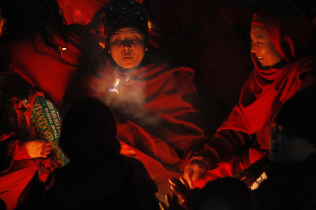 Nepalese women devotees sit around a bonfire  to warm themselves before they take holy deep in Salinadi River during the first day of month long Swasthani Bratakatha festiva in Sankhu, on the outskirts of Katmandu, Monday, January 5, 2015. During this month-long festival, devotees recite Holy Scriptures dedicated to Hindu goddess Swasthani and Lord Shiva. Unmarried women pray to have a good husband while those married pray for the longevity of their husbands by observing a month-long fast. (Photo by Niranjan Shrestha/AP Photo)