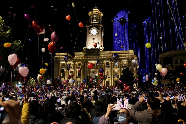 People hold balloons as they gather to celebrate the arrival of the new year in Wuhan, China on December 31, 2020. (Photo by Tingshu Wang/Reuters)