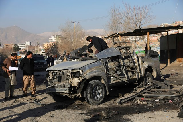 Afghan security personnel inspect the site of a bombing attack in Kabul, Afghanistan, Wednesday, December 16, 2020. A bombing attack on Wednesday in the Afghan capital of Kabul wounded a few people, Ferdaws Faramarz, a spokesman for the Kabul police chief said. (Photo by Rahmat Gul/AP Photo)