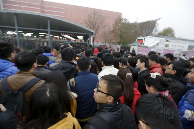 An Zi waits in a line outside a subway station on his way to work around 7:30 am in Changping district, on the outskirts of Beijing, China, November 12, 2015. (Photo by Jason Lee/Reuters)