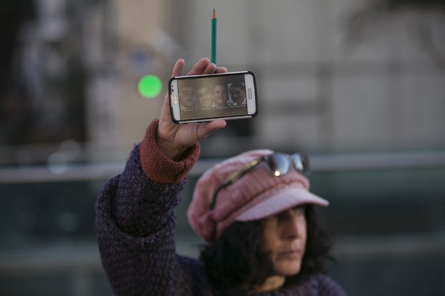 A woman holds up a pencil and her phone displaying pictures of the victims of an attack on a kosher supermarket at Porte de Vincennes near Paris, during a rally in Tel Aviv, January 11, 2015, in tribute to this week's victims of the shootings by gunmen at the Paris offices of the satirical weekly newspaper Charlie Hebdo. (Photo by Baz Ratner/Reuters)