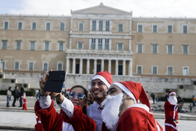 "People dressed in Santa costumes take a ""selfie"" in front of the parliament building as they take part in the Santa Claus Run in Athens, Greece, November 29, 2015. (Photo by Alkis Konstantinidis/Reuters)"