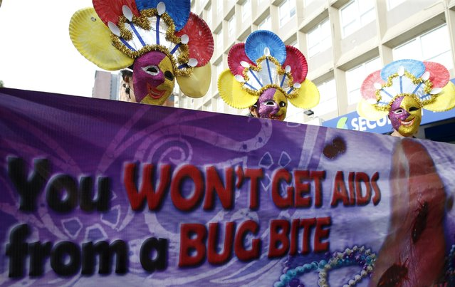 Government health workers wear masks as they display a streamer during a World Aids Day celebration in Manila, Philippines, December 1, 2015. (Photo by Erik De Castro/Reuters)
