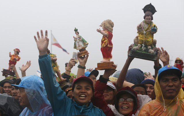 People raise religious statues before an open-air Mass led by Pope Francis in Manila January 18, 2015. (Photo by Paul Barker/Reuters)