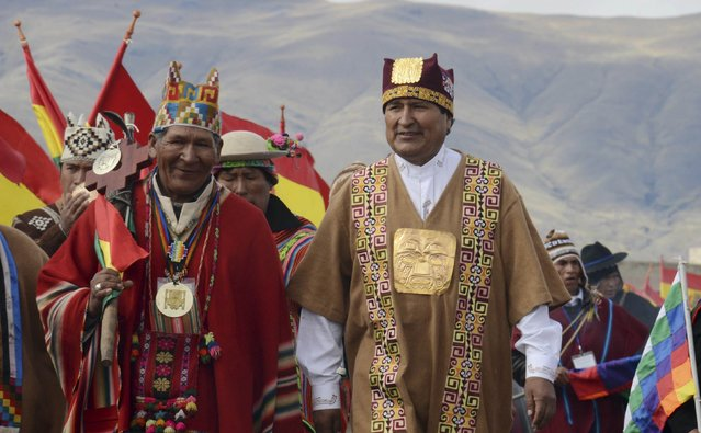 Bolivia's President Evo Morales (R) wears ceremonial clothes as he participates in a ceremony in Tiahuanaco, some 70 km from La Paz, in this January 21, 2015 handout photo provided by the Bolivian Presidency. (Photo by Reuters/ABI/Bolivian Presidency)