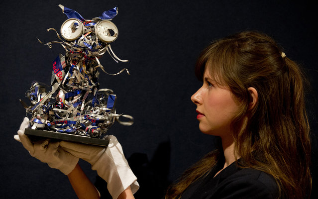 """A gallery assistant holds """"My Cat Docket"""" by British artist Tracy Emin ahead of its sale at Bonhams auction house in London on June 24, 2013. (Photo by Justin Tallis/AFP Photo)"""