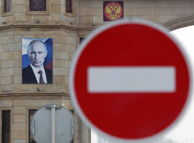 Road signs are pictured in front of an arch with a portrait of Russia's President Vladimir Putin at the entrance to the town of Argun, outside Grozny, January 20, 2015. Picture taken January 20, 2015. (Photo by Eduard Korniyenko/Reuters)