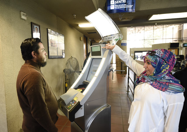 Contractor Sabira Dewji, right, helps a pedestrian crossing from Mexico into the United States at the Otay Mesa Port of Entry have his facial features and eyes scanned at a biometric kiosk Thursday, December 10, 2015, in San Diego. On Thursday, U.S. Customs and Border Protection began capturing facial and eye scans of foreigners entering the country at San Diego's Otay Mesa port of entry on foot. (Photo by Denis Poroy/AP Photo)