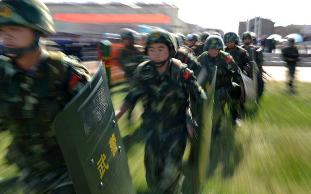 """An anti-terrorism force including public security police and the armed police attend an anti-terrorism joint exercise in Hami, northwest China's Xinjiang region on July 2, 2013. The United States is encouraging """"terrorism"""" in Xinjiang, Chinese state media said on July 1, also claiming that separatists in the region – which has a large Uighur minority – had fought alongside Syrian rebels. (Photo by AFP Photo)"""