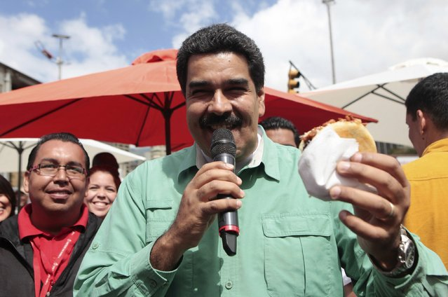 Venezuela's President Nicolas Maduro eats a traditional arepa while visiting a market in downtown Caracas January 24, 2015. (Photo by Miraflores Palace/Reuters)