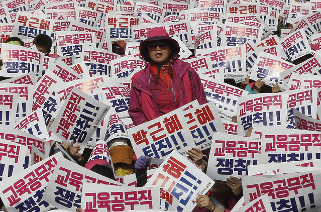 """A South Korean protester stands as her colleagues hold up cards during a rally calling for South Korean President Park Geun-hye to step down in Seoul, South Korea, Saturday, November 12, 2016. Tens, and possibly hundreds, of thousands of South Koreans were expected to rally in Seoul on Saturday demanding the ouster of Park in what would be one of the biggest protests in the country since its democratization about 30 years ago. The signs read """"Park Geun-hye should step down"""". (Photo by Ahn Young-joon/AP Photo)"""
