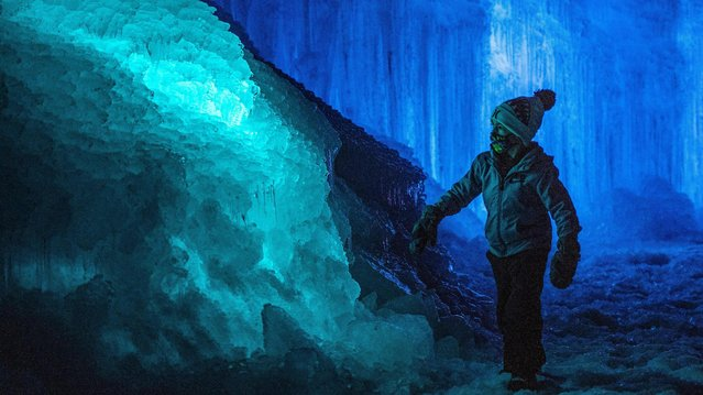 A child explores the ice walls, tunnels and lights at Ice Castles in North Woodstock, New Hampshire, on January 14, 2021. Hundreds of people attended the sold out opening night that was delayed by two weeks due to warm weather and rain. (Photo by Joseph Prezioso/AFP Photo)