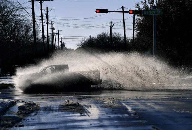A pickup sends a wake of snow melt high into the air as the driver plows through a large puddle at Barrow and South 11th streets intersection in Abilene, Texas, Friday, February 19, 2021. Temperatures climbed above freezing for the first time since Sunday's record 14.8-inch snowfall. (Photo by Ronald W. Erdrich, The Abilene Reporter-News via AP Photo)