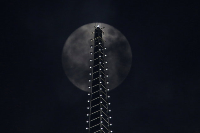 The supermoon is seen behind a building in Shanghai, China November 14, 2016. (Photo by Aly Song/Reuters)