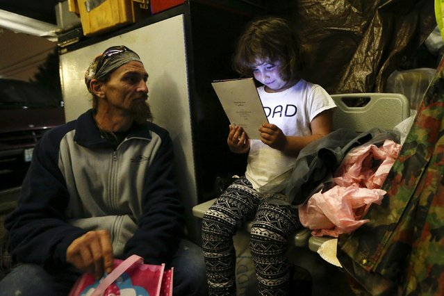 Emma Savage, 6, opens a birthday card given to her by her dad Robert Rowe, 42, a day labourer who had just returned from a 12-hour working day to SHARE/WHEEL Tent City 3 outside Seattle, Washington October 12, 2015. (Photo by Shannon Stapleton/Reuters)