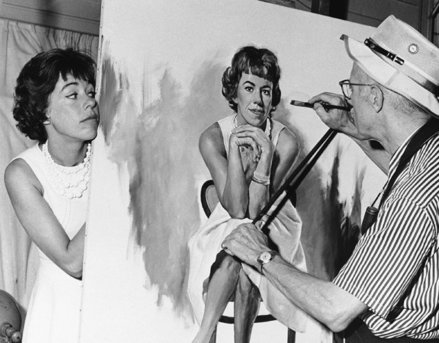 Actress-comedian Carol Burnett peeks around canvas to watch artist Dmitri Vails work on her portrait on January 9, 1963. The Dallas, Texas portrait painter has become well known as a painter of people in show business. (Photo by AP Photo)