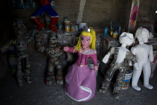 In this January 20, 2015 photo, a piñata resembling Sleeping Beauty stands among other partially finished piñatas, inside the workshop of Melesio Vicente Flores and his wife Cecilia Albarran Gonzalez, in the Iztapalapa neighborhood of Mexico City. Piñata vendors keep the craftsmen apprised of the market. Perennial favorites among the different figures include Spiderman, Mickey Mouse and Buzz Lightyear. (Photo by Rebecca Blackwell/AP Photo)