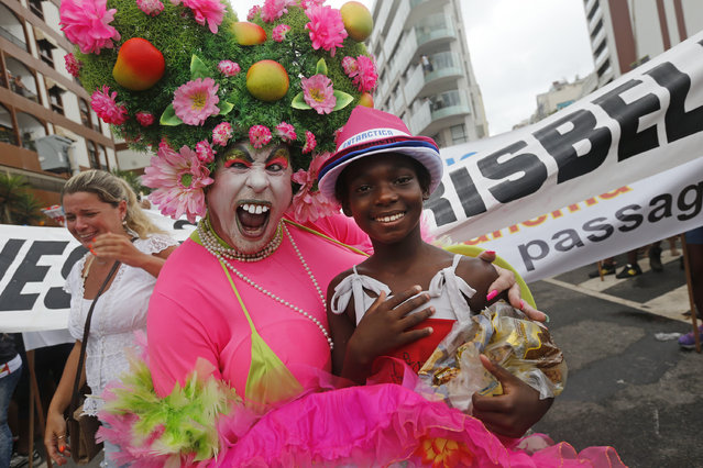 "A reveler and a child street vendor pose for a photo during the Banda de Ipanema Carnival parade in Rio de Janeiro, Brazil, Saturday, January 31, 2015. Rio's over-the-top Carnival is the highlight of the year for many local residents. Hundreds of thousands of merrymakers are beginning to take to the streets in open-air ""blocos"" parties. (Photo by Silvia Izquierdo/AP Photo)"