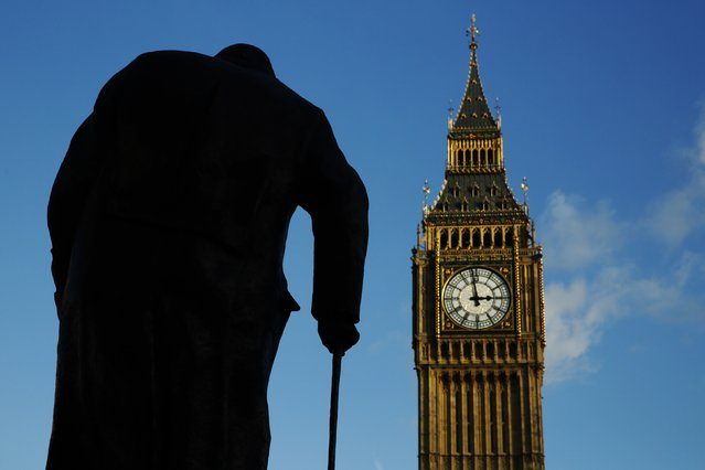 The statue of Britain's former Prime Minister Winston Churchill is silhouetted in front of the Houses of Parliament in London January 24, 2015. Today is the 50th anniversary of the World War Two statesman's death. (Photo by Luke MacGregor/Reuters)
