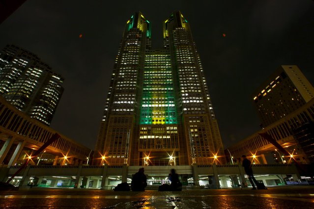 The Tokyo Municipal Government Headquarters are pictured lit in the yellow and green colours of Brazil's flag in celebration of the 100 days before the 2016 Rio Olympics in Tokyo, Japan, April 27, 2016. (Photo by Thomas Peter/Reuters)