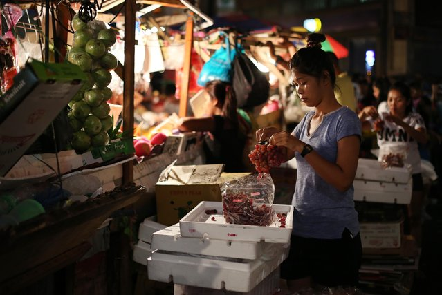 Sherry-Ann Abellar prepares grapes in her makeshift family-run fruit stall in downtown Manila, Philippines, on Monday, December 28, 2015. Many Filipinos believe that having 12 round fruits of different kinds on the family table will bring good luck during the New Year. (Photo by Aaron Favila/AP Photo)