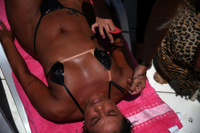 Erika, owner of the Erika Bronze spa, takes off the masking tape bikini from a client's body after sunbathing on a terrace to have the perfect bikini line ('marquinha' in Portuguese), in Rio de Janeiro, Brazil, November 17, 2016.  Women start arriving at the spa between 7am and 8am and will tan for approximately 3 hours. (Photo by Pilar Olivares/Reuters)