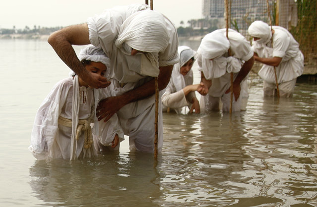 """Followers of the Sabean Mandaeans, a pre-Christian sect that follows the teachings of John the Baptist, perform their rituals in the Tigris river during a celebration marking """"Banja"""" or Creation Feast in central Baghdad, Iraq, Monday, March 15, 2021. Iraqi Sabaean Mandeans view the Bible's John the Baptist as savior and submerge themselves in the Tigris in an annual five-day ritual. (Photo by Hadi Mizban/AP Photo)"""