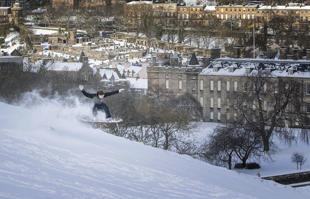 Kyle Hamilton snowboards down Saliisbury Crags in Holyrood Park, Edinburgh, Scotland, as the cold snap continues to grip much of the nation, Wednesday, February 10, 2021. (Photo by Jane Barlow/PA Wire via AP Photo)