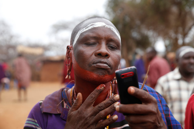 A Maasai man uses a phone to paint himself with a red ochre pigment during an initiation into an age group ceremony near the town of Bisil, Kajiado county, Kenya on August 23, 2018. (Photo by Baz Ratner/Reuters)