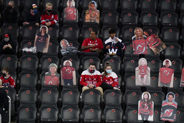 In this April 4, 2021, file photo, Washington Capitals fans sit among cutouts of New Jersey Devils fans as they watch the second period of an NHL hockey game between the Devils and the Capitals in Newark, N.J. Nearly half of new coronavirus infections nationwide are in just five states, including New Jersey – a situation that puts pressure on the federal government to consider changing how it distributes vaccines by sending more doses to hot spots. (Photo by Frank Franklin II/AP Photo)