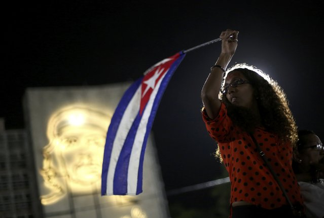 A mourner waves a Cuban flag while attending a tribute to Cuba's late President Fidel Castro at Revolution Square in Havana, Cuba, November 29, 2016. (Photo by Edgard Garrido/Reuters)