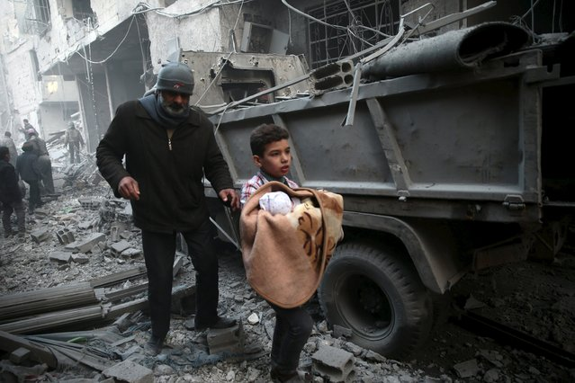 A boy carries a baby in a site hit by what activists said were airstrikes carried out by the Russian air force in the town of Douma, eastern Ghouta in Damascus, Syria January 10, 2016. (Photo by Bassam Khabieh/Reuters)