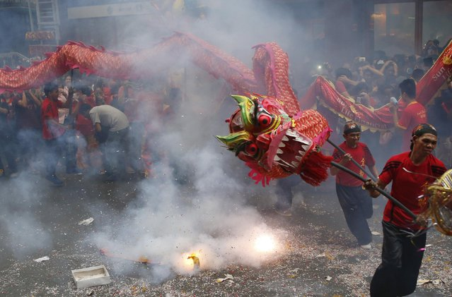 People perform a dragon dance amidst exploding firecrackers as they celebrate Lunar New Year at Manila's Chinatown February 19, 2015. (Photo by Erik De Castro/Reuters)