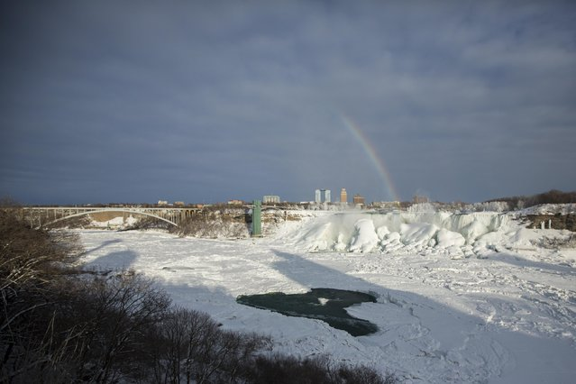 A rainbow appears over the partially frozen American Falls (R) in sub freezing temperatures in Niagara Falls, Ontario February 17, 2015. (Photo by Lindsay DeDario/Reuters)