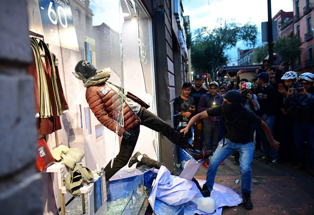 Hooded demonstrators vandalise a shop window in Mexico City, during the commemoration of the 50th anniversary of the 1968 Tlatelolco student massacre, on October 2, 2018. Fifty years ago, Mexican troops opened fire on student demonstrators, killing hundreds just days before Mexico City hosted the 1968 Olympics – one of the darkest episodes in a year of global turbulence. (Photo by Ronaldo Schemidt/AFP Photo)