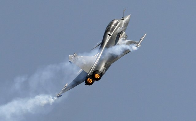 Rafale, a French fighter aircraft flies over static display area on the final day of Aero India air show at Yelahanka air base in Bangalore, India, Sunday, February 22, 2015. Aero India is a biennial event with flying demonstrations by stunt teams and militaries and commercial pavilions where aviation companies display their products and technology. (Photo by Aijaz Rahi/AP Photo)
