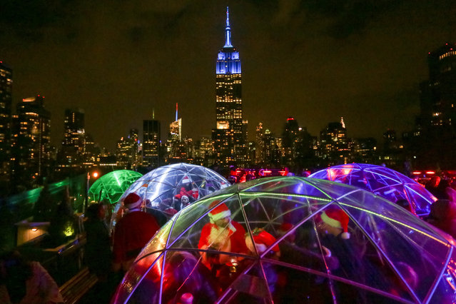 The Empire State Building is seen in the background as revellers take part in the annual SantaCon event in Manhattan, New York, December 10, 2016. (Photo by Jeenah Moon/Reuters)