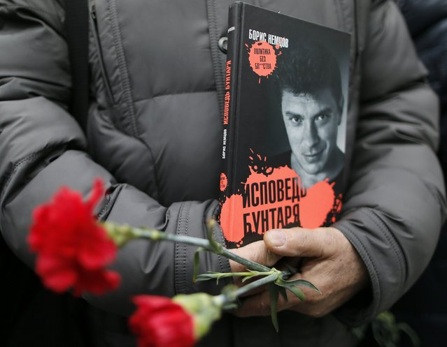 "A visitor holds flowers and a book ""Confessions of the Rebel"" by Russian leading opposition figure Boris Nemtsov while waiting to attend a memorial service before the funeral of Nemtsov in Moscow, March 3, 2015. Nemtsov's girlfriend has broken her public silence on the murder of the Russian opposition activist, saying she did not see the killer who gunned him down as they strolled across a bridge near the Kremlin. Anna Duritskaya, who is 23 or 24, said she had been under constant guard since the murder and would probably be unable to attend Nemtsov's funeral on Tuesday. REUTERS/Maxim Shemetov"