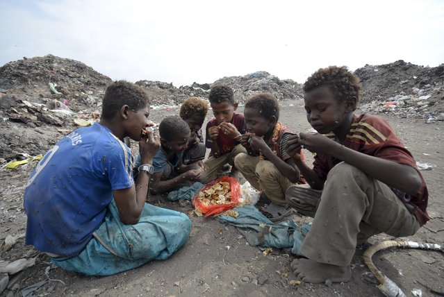 Boys eat at a rubbish dump where they are collecting recyclable waste outside Yemen's Red Sea port city of Houdieda January 20, 2016. (Photo by Abduljabbar Zeyad/Reuters)